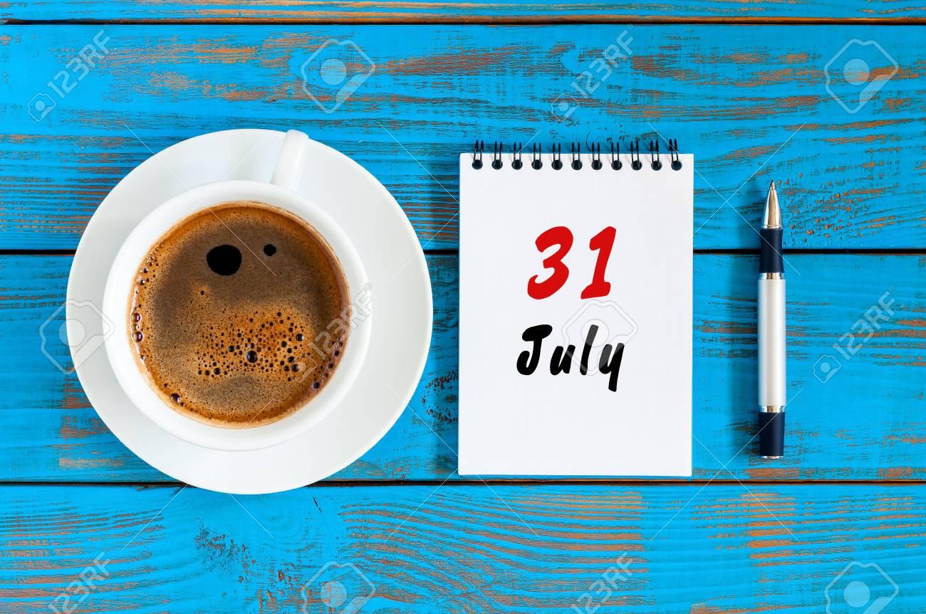 Calendario 31 Luglio.31 Luglio Giorno 31 Del Mese Calendario Su Sfondo Blu Tavolo In Legno Con Tazza Di Caffe Al Mattino Concetto Di Estate