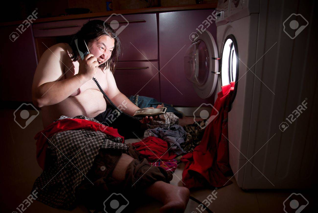 Asian fat man speak on the telephone near washing machine glowing inside Stock Photo - 9265227