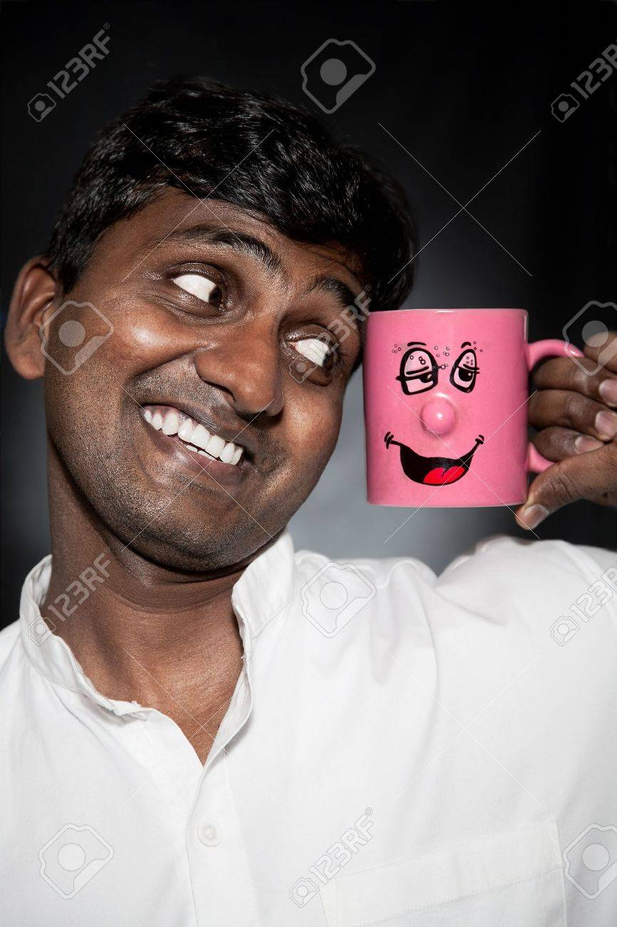 Handsome Indian man with funny mug smiling and looking at it close-up Stock Photo - 9257323