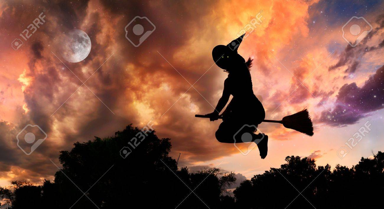 Halloween witch silhouette with glowing eyes flying on broomstick in the evening at dramatic sky with moon and stars Stock Photo - 10772564