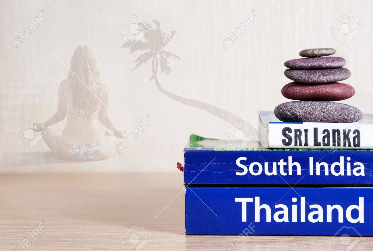 Guide books on the table with ayurveda massage stones on its. Woman in yoga meditation with palm tree at background. Books with titles: South India, Sri Lanka, Thailand Stock Photo - 10772559
