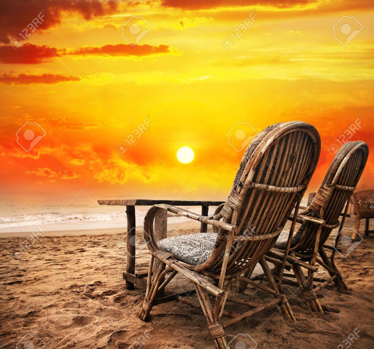 Beach sunset with chairs - Two Chairs With View To The Orange Sunset Sky And Ocean In Goa India Stock