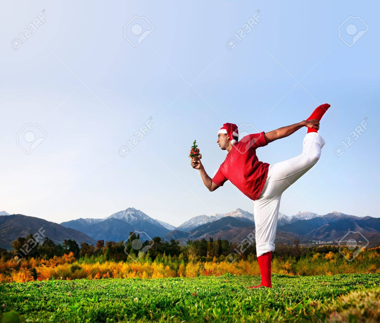 Christmas yoga natarajasana dancer pose by funny Indian man in white trousers, red socks and Christmas hat with looking at Christmas tree at mountain background. Free space for text Stock Photo - 11270307