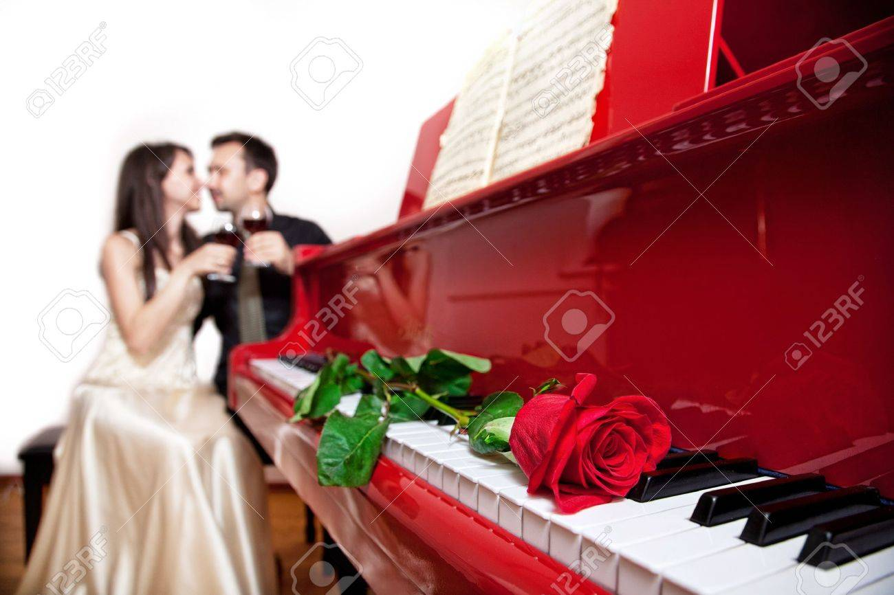 Red rose on the red grand piano keyboard in focus and couple sitting on the chair with glasses of wine at background Stock Photo - 11915978