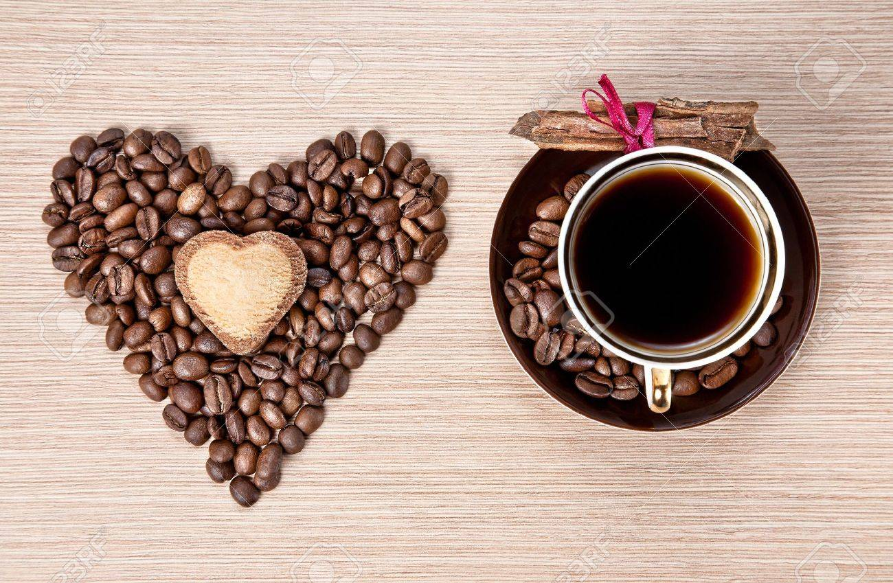 Cup of Coffee and grains in shape of heart with cookie on it and cinnamon bark wrapped with red ribbon on the saucer. Represent Valentines day Stock Photo - 11915991