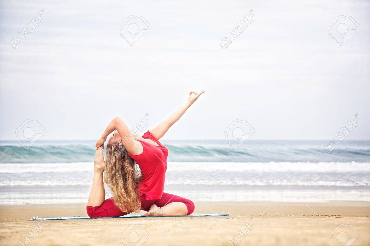 Yoga raja kapotasana dove pose by young woman with long hair in red cloth on the beach at ocean background Stock Photo - 14428592
