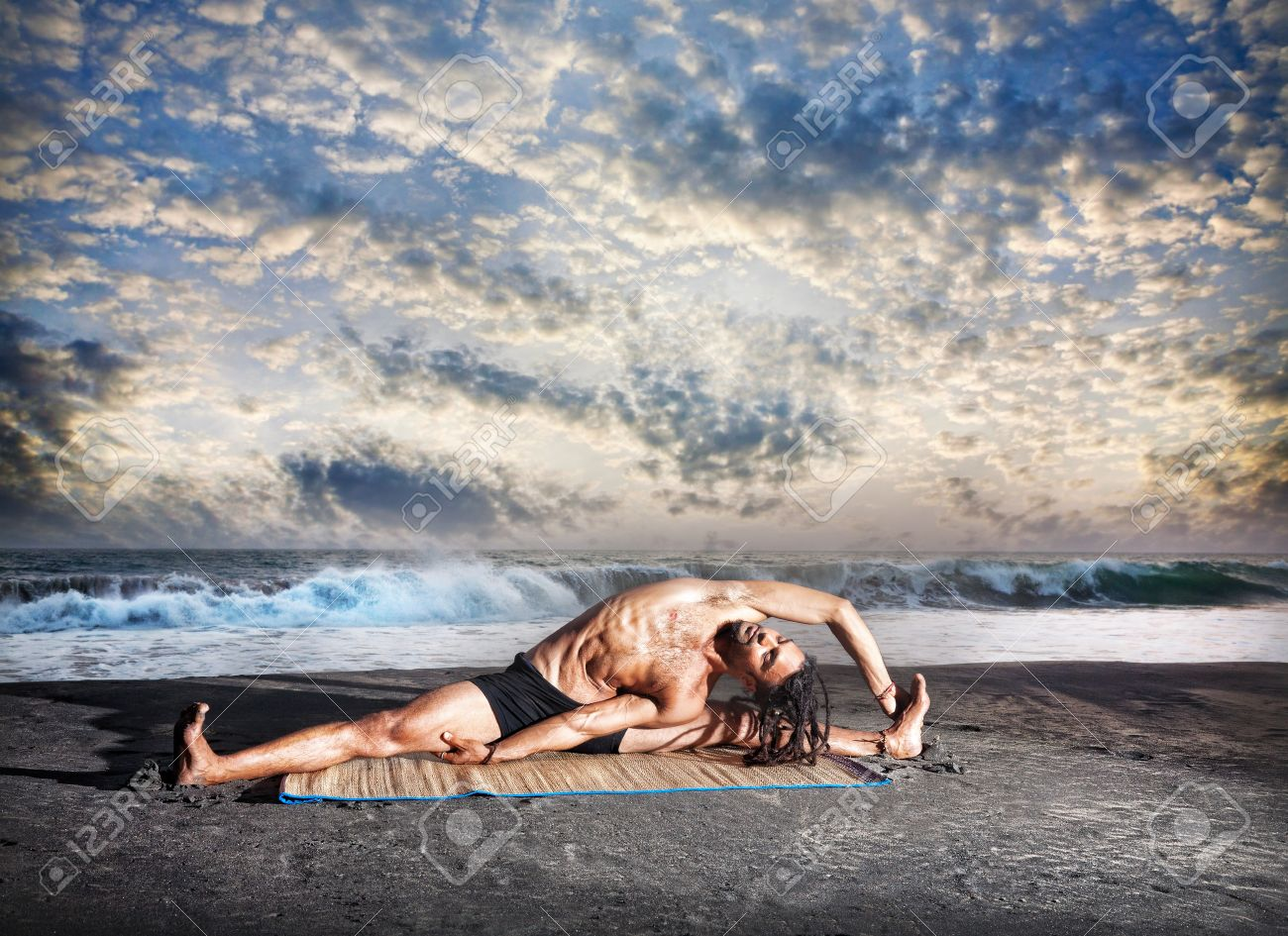 Yoga parivrtta janu sirsasana pose by fit man with dreadlocks on the beach near the ocean at sunset background Stock Photo - 14471335