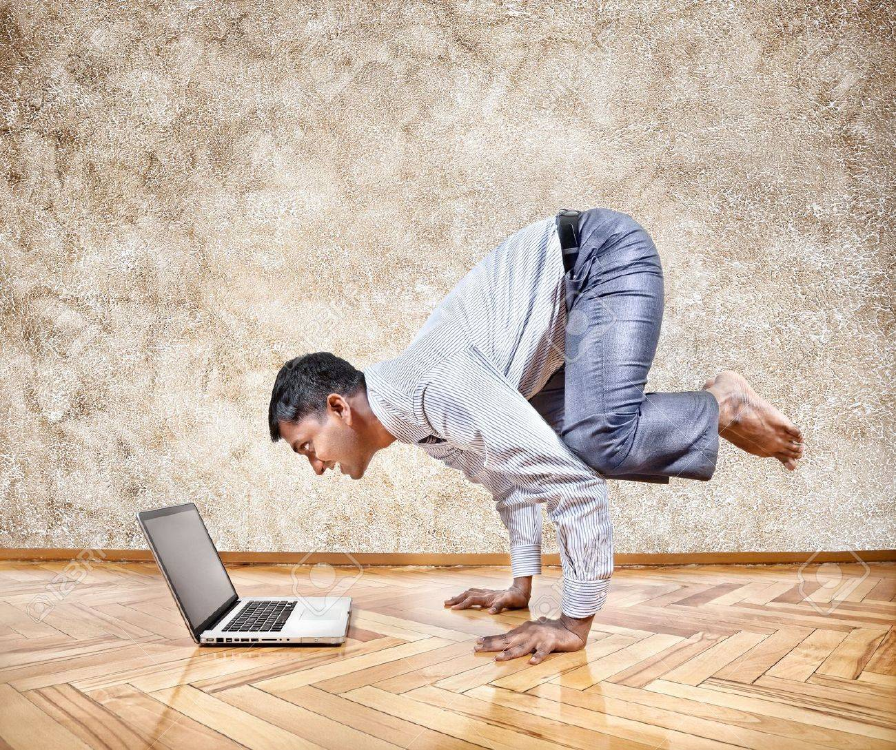 Indian businessman doing yoga hand stand pose and looking at his laptop in the office at brown textured background Stock Photo - 17054923