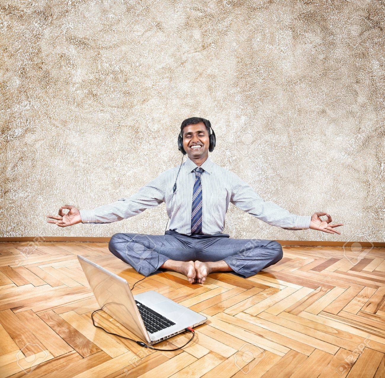 Indian businessman listening to the music with headphones and doing meditation near the laptop Stock Photo - 20047808