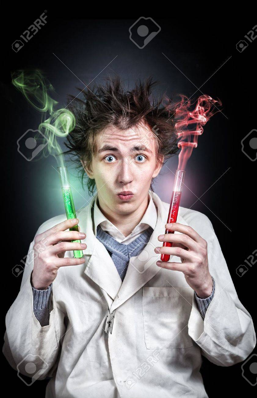 Crazy young doctor holding two test tubes with red and green liquid at black background Stock Photo - 20670716