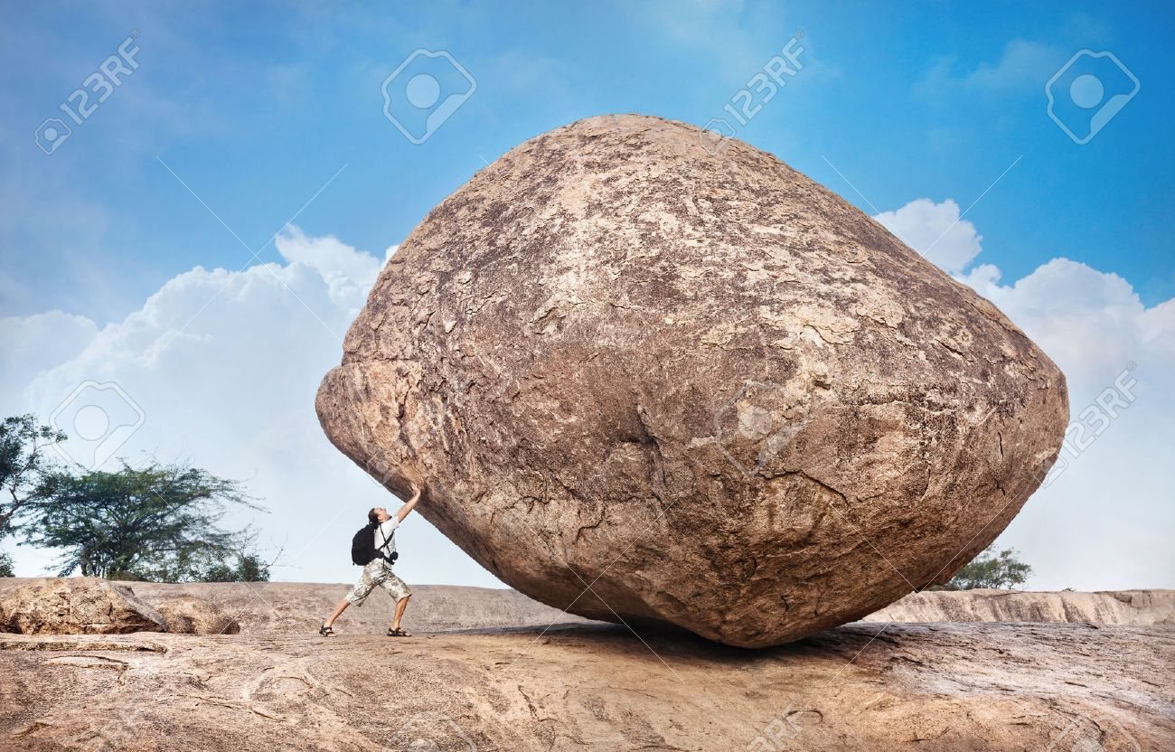 Man with backpack pushing a huge stone in Mamallapuram cave complex, Tamil Nadu, India Stock Photo - 23811232