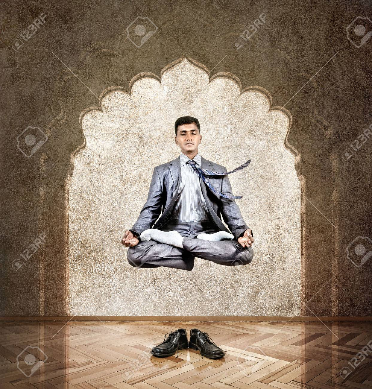 meditation office. indian businessman doing meditation in the air lotus pose at office with arch on