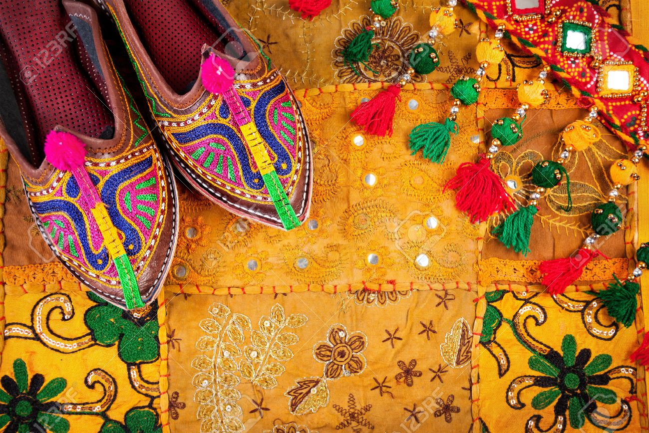 Colorful ethnic shoes and gipsy belt on yellow Rajasthan cushion cover on flea market in India Stock Photo - 39056066