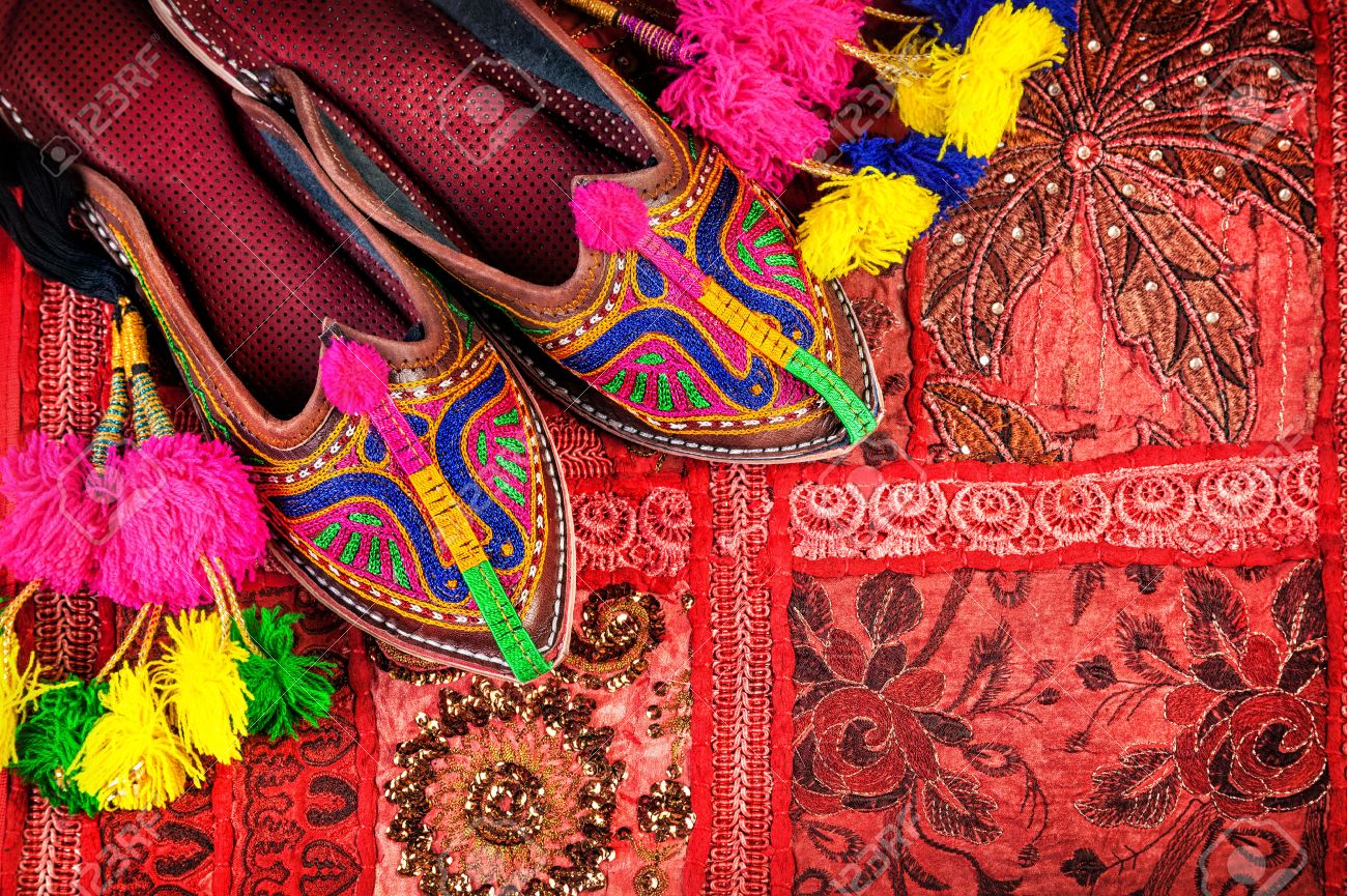 Colorful Ethnic Shoes And Camel Decorations On Red Rajasthan