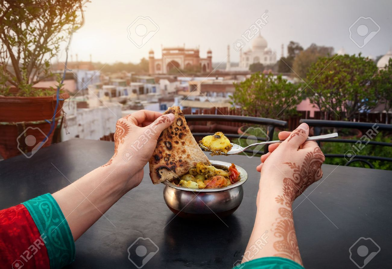 Woman eating traditional Indian food in rooftop restaurant with Taj Mahal view in Agra, Uttar Pradesh, India Stock Photo - 40091839