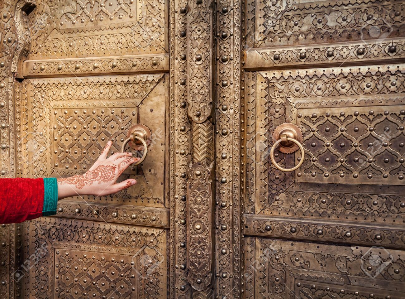 Woman hand with henna painting opening golden door in City Palace of Jaipur, Rajasthan, India Stock Photo - 40347668
