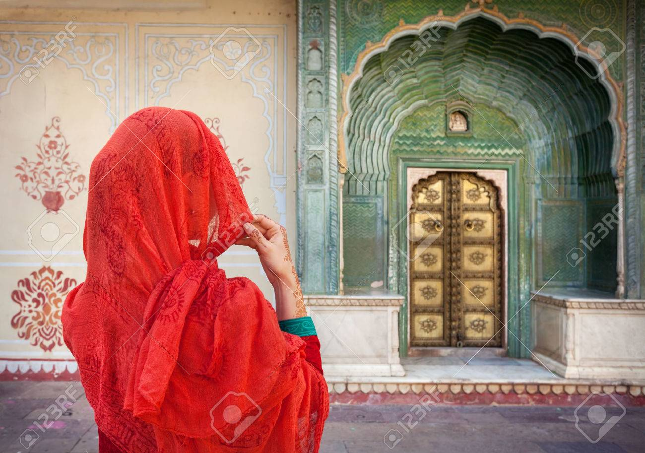 Woman in red scarf looking at green gate door in City Palace of Jaipur, Rajasthan, India Stock Photo - 40347671