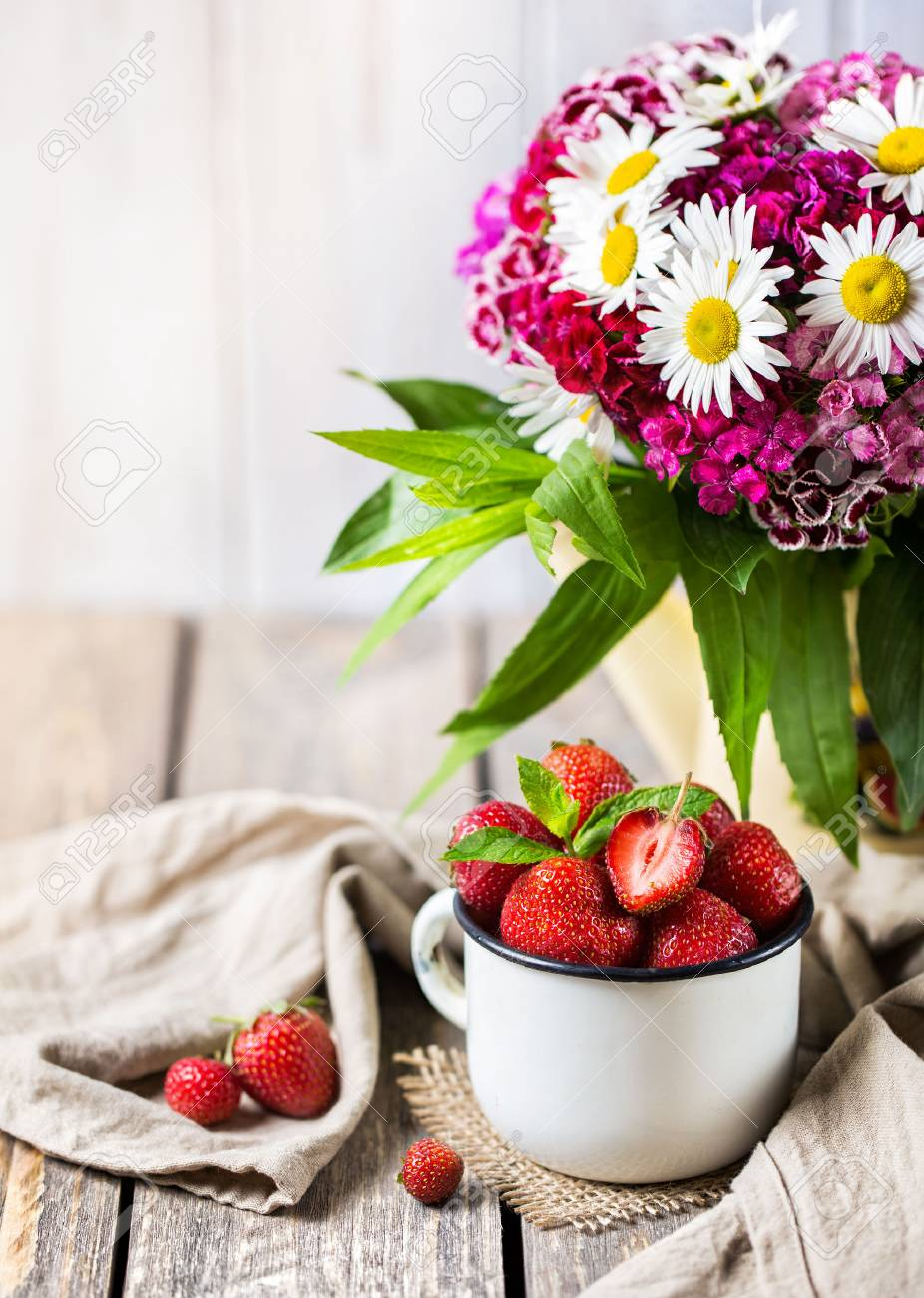 Strawberry In The Cup Near Flower Bouquet On Wooden Table Stock ...