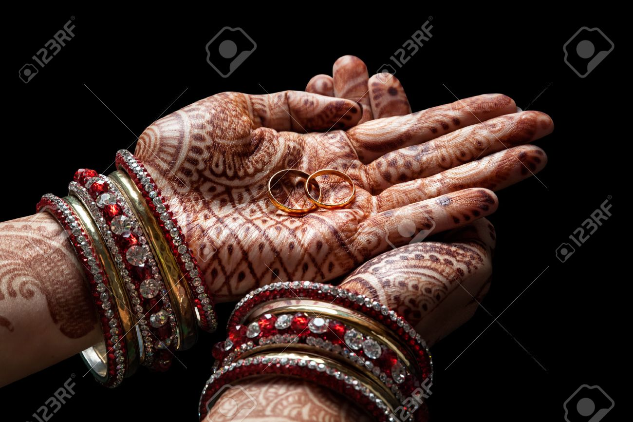 Woman hands with henna holding two golden wedding rings on black background Stock Photo - 41075871