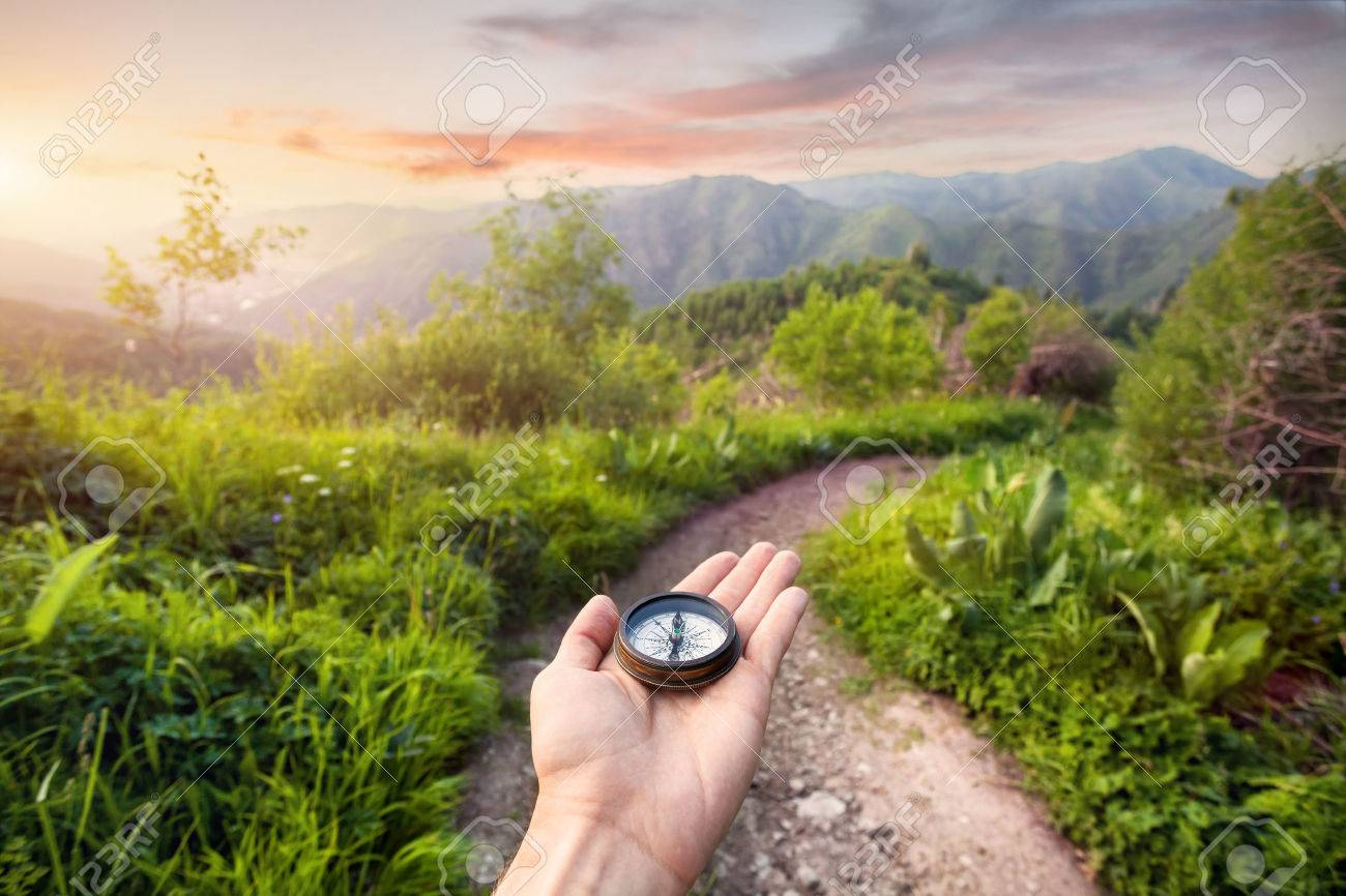 Hand with compass at mountain road at sunset sky in Kazakhstan, central Asia Stock Photo - 41474511
