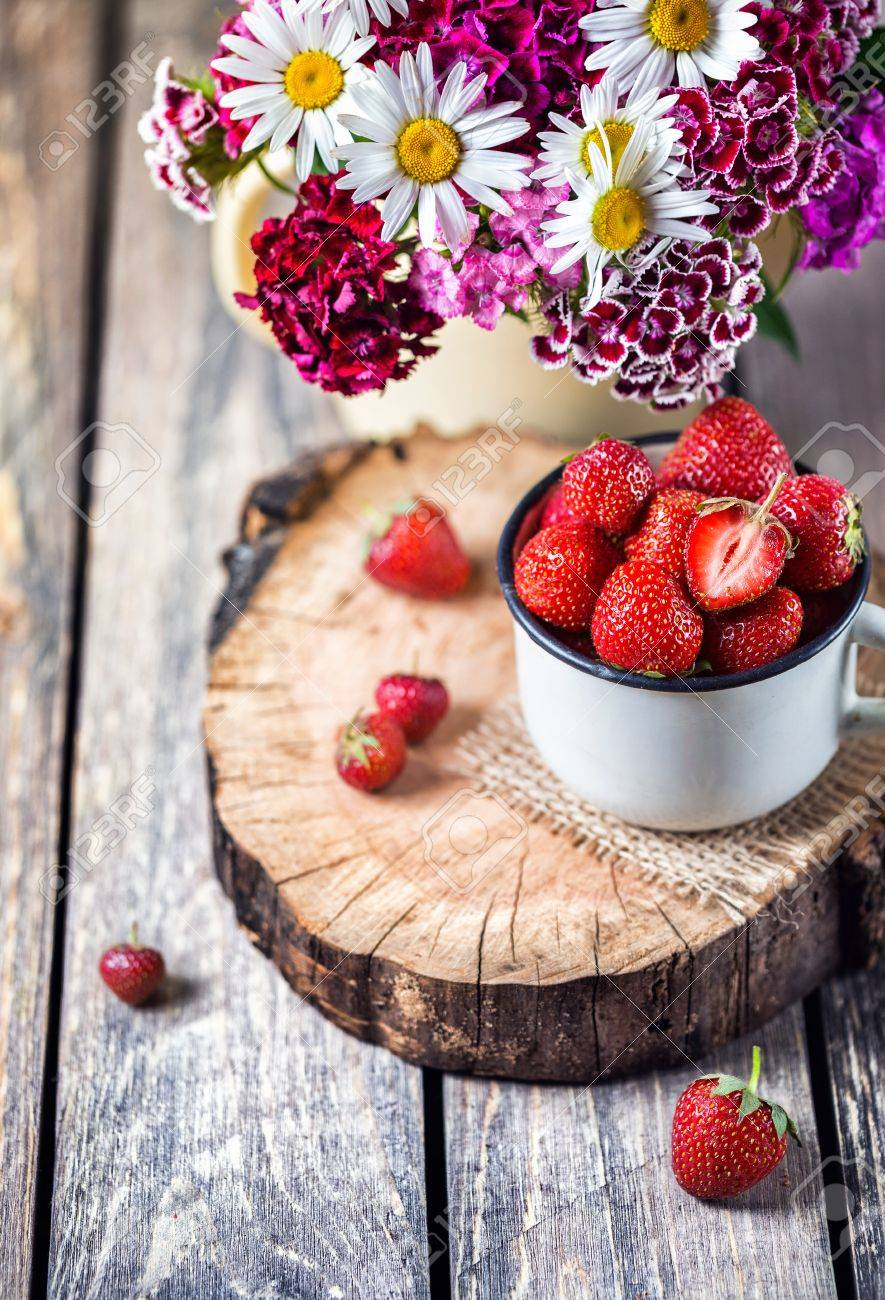 Strawberry In The Cup Near Flower Bouquet On Wooden Table Stock Photo Picture And Royalty Free Image Image 41795715