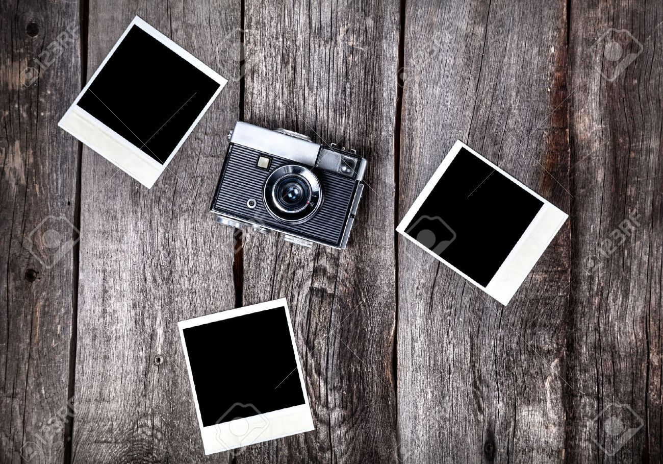 Old film camera and polaroid photos with space for pictures on the wooden background Stock Photo - 42066598