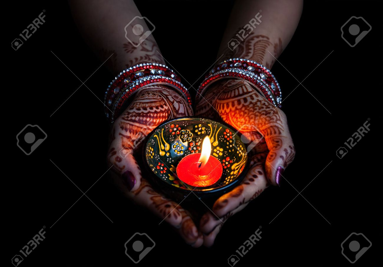 Woman hands with henna holding lit candle isolated on black background with clipping path Stock Photo - 42855543