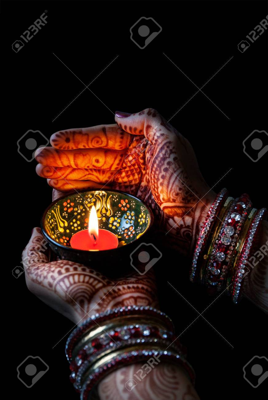 Woman hands with henna holding lit candle isolated on black background with clipping path Stock Photo - 42855593