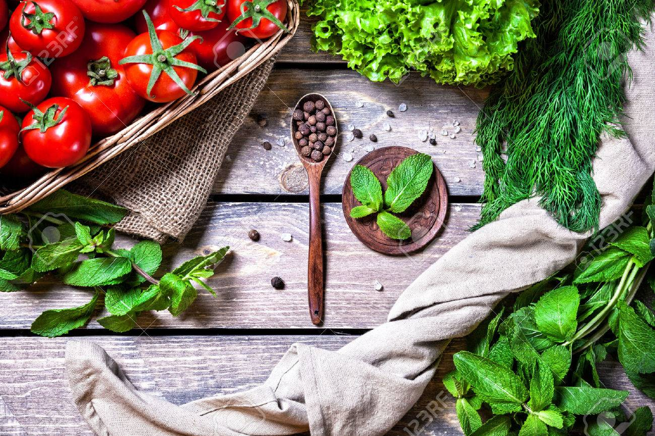 Spoon with black pepper, tomato, herbs and green salad on the wooden table in the kitchen Stock Photo - 43839265