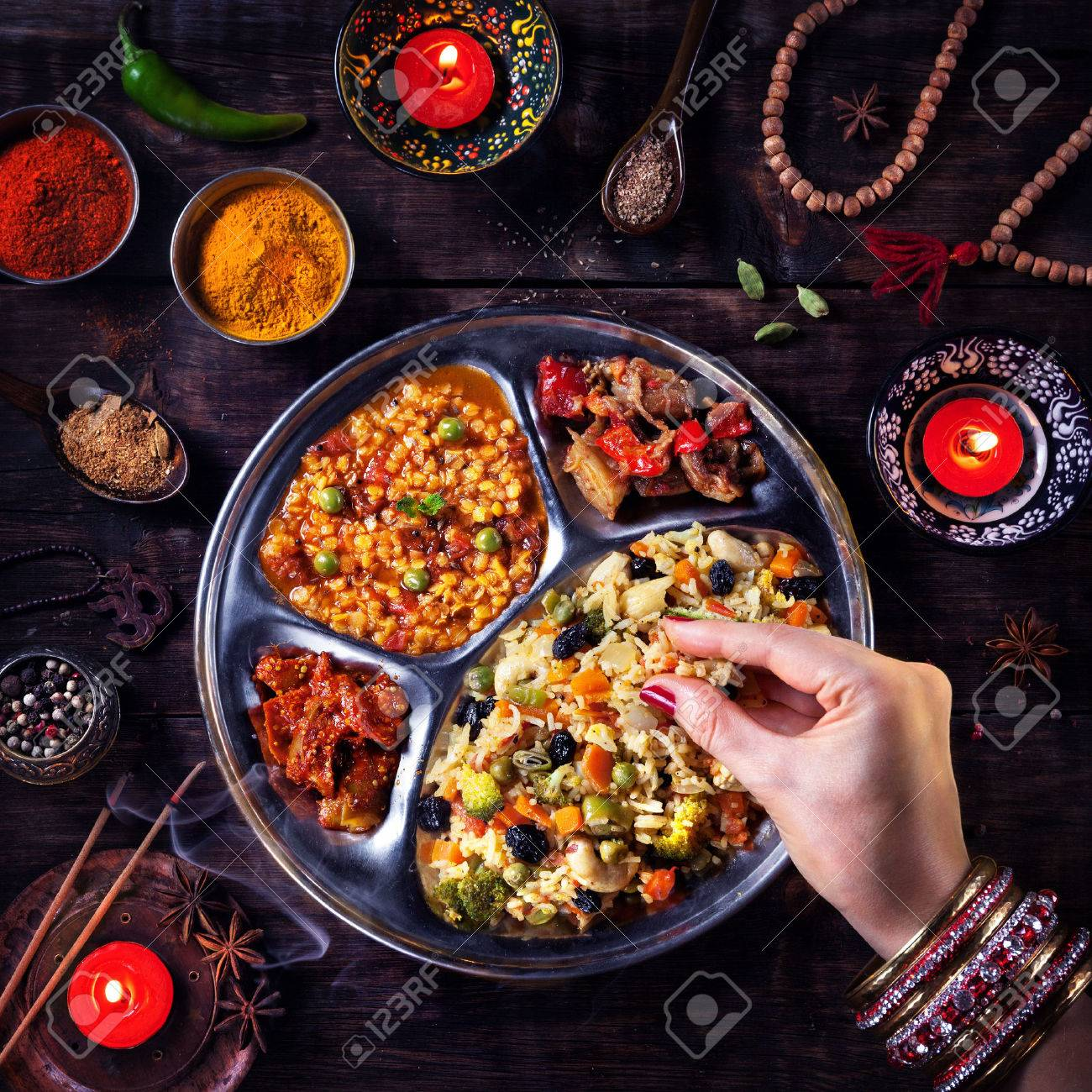 Woman eating vegetarian biryani by her hand with bangles near candles, incense and religious symbols at Diwali celebration Stock Photo - 45388774