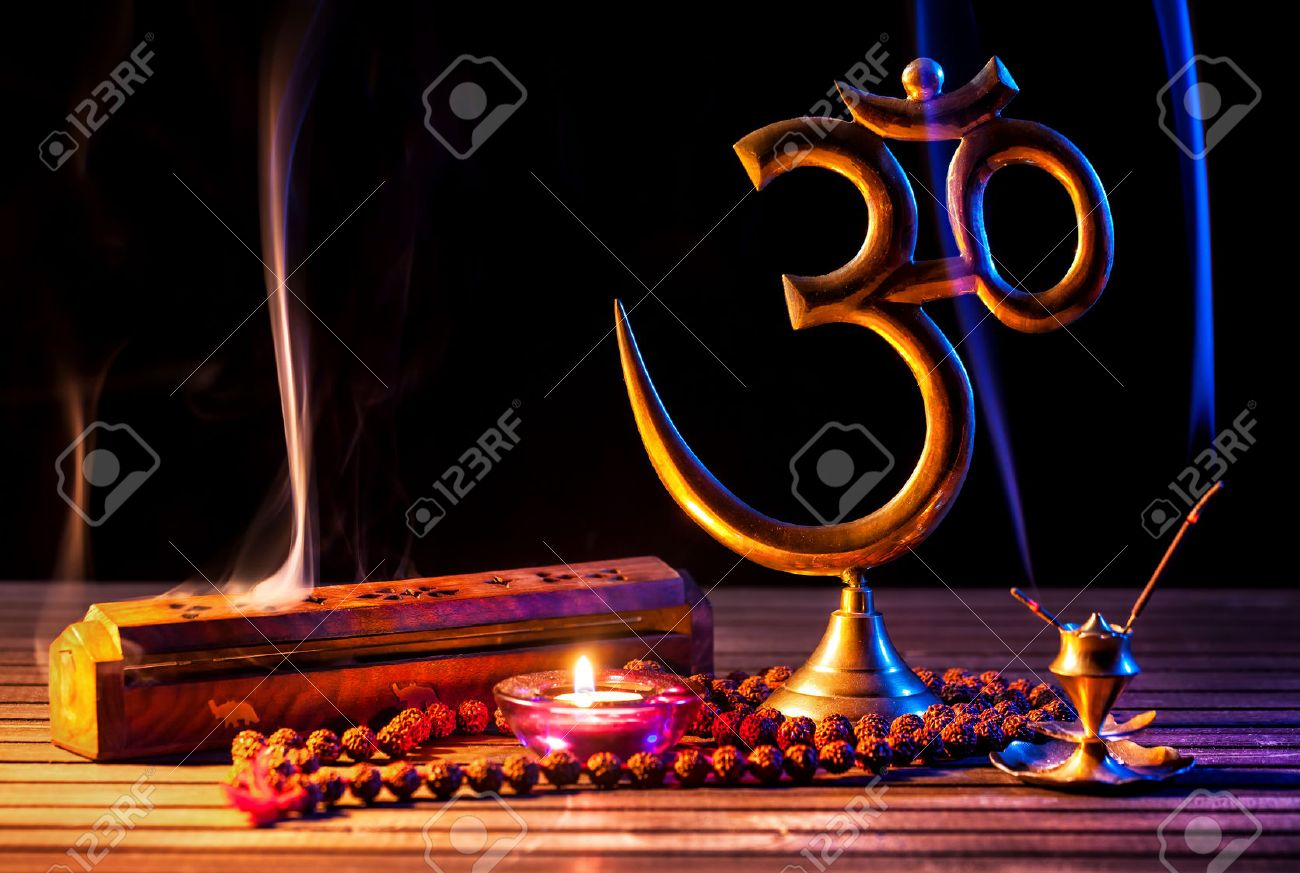 Om symbol, incense smoke, candle and japa mala on wooden table at black background Stock Photo - 46400577