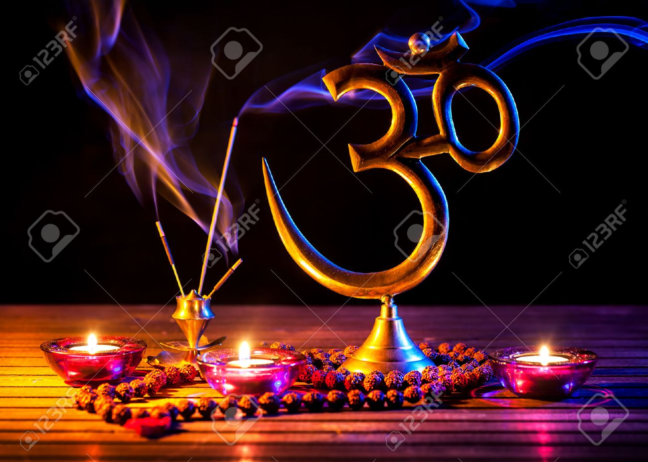 Om symbol, incense smoke, candle and japa mala on wooden table at black background Stock Photo - 46490811