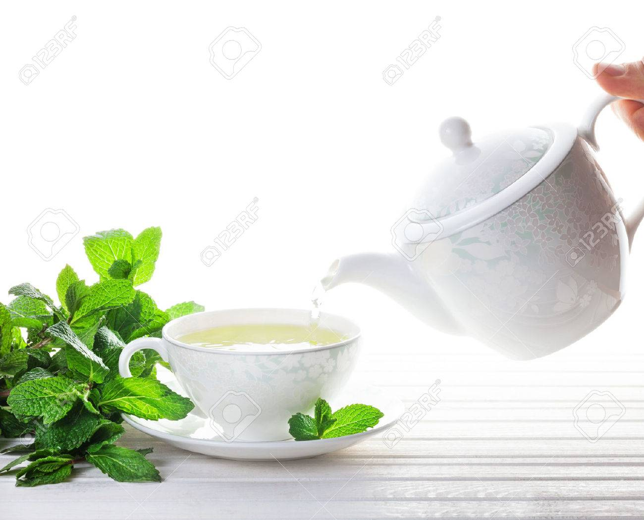 Mint tea pouring out from teapot in the cup near mint leaves at white background Stock Photo - 47255701