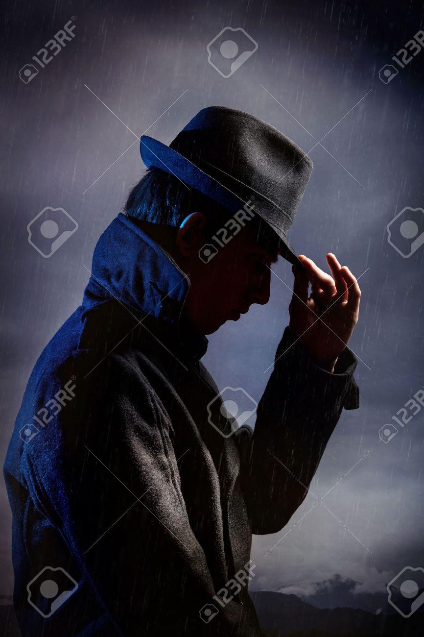 Man in black hat in the rain at dark overcast sky Stock Photo - 46798061