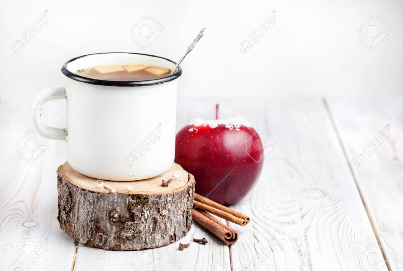 Hot beverage from apples and spices on white wooden background at Christmas time Stock Photo - 47866586
