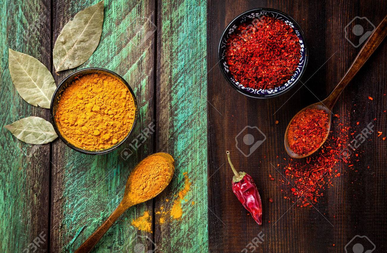 Chili, paprika, turmeric and bay leaves on wooden green and brown background Stock Photo - 47982604