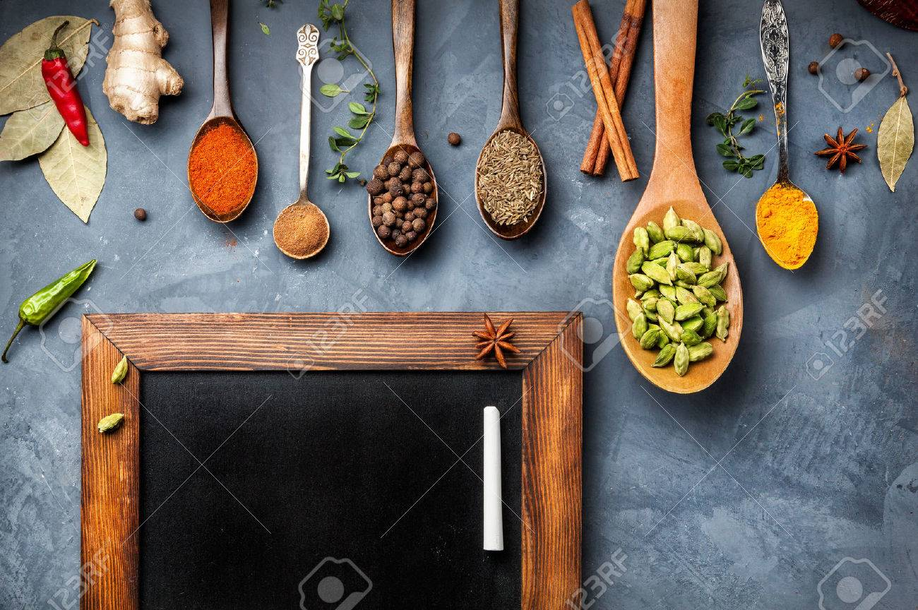 Various Spices like turmeric, cardamom, chili, ginger, star anise and cinnamon near blackboard on grunge background. Free space for your text Stock Photo - 47982634