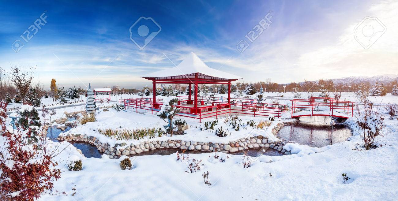 winter japanese garden with red pagoda at mountains and blue
