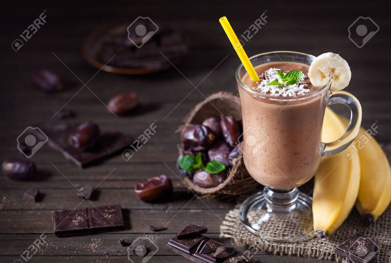Sweet chocolate banana smoothie with coconut milk and dates decorated with mint leaves on wooden background Stock Photo - 50396747