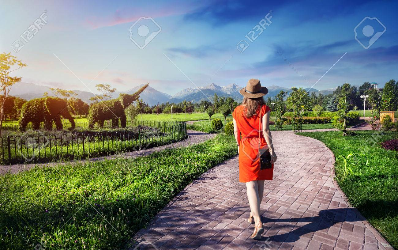 Woman in orange dress walking down the road in Topiary Garden with elephants from plants - 60232468