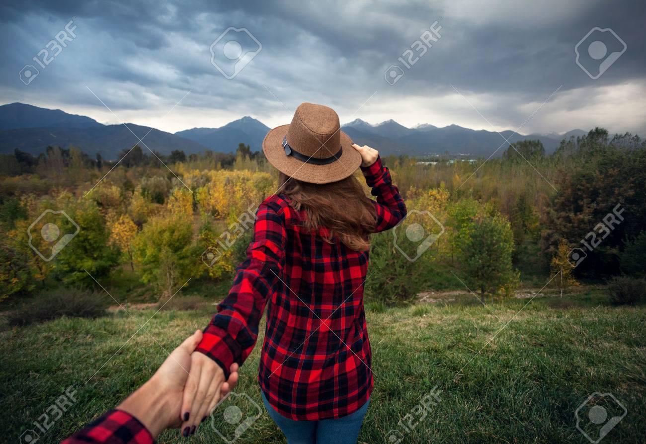 fdd316e381052 Foto de archivo - Mujer en rojo camisa a cuadros y un sombrero holding  hombre con la mano va a Bosque del otoño con las montañas y el cielo nublado