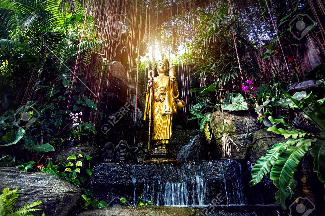 Golden Buddha statue in the tropical garden with waterfall in Wat Saket Golden Mountain Temple in Bangkok - 74709924