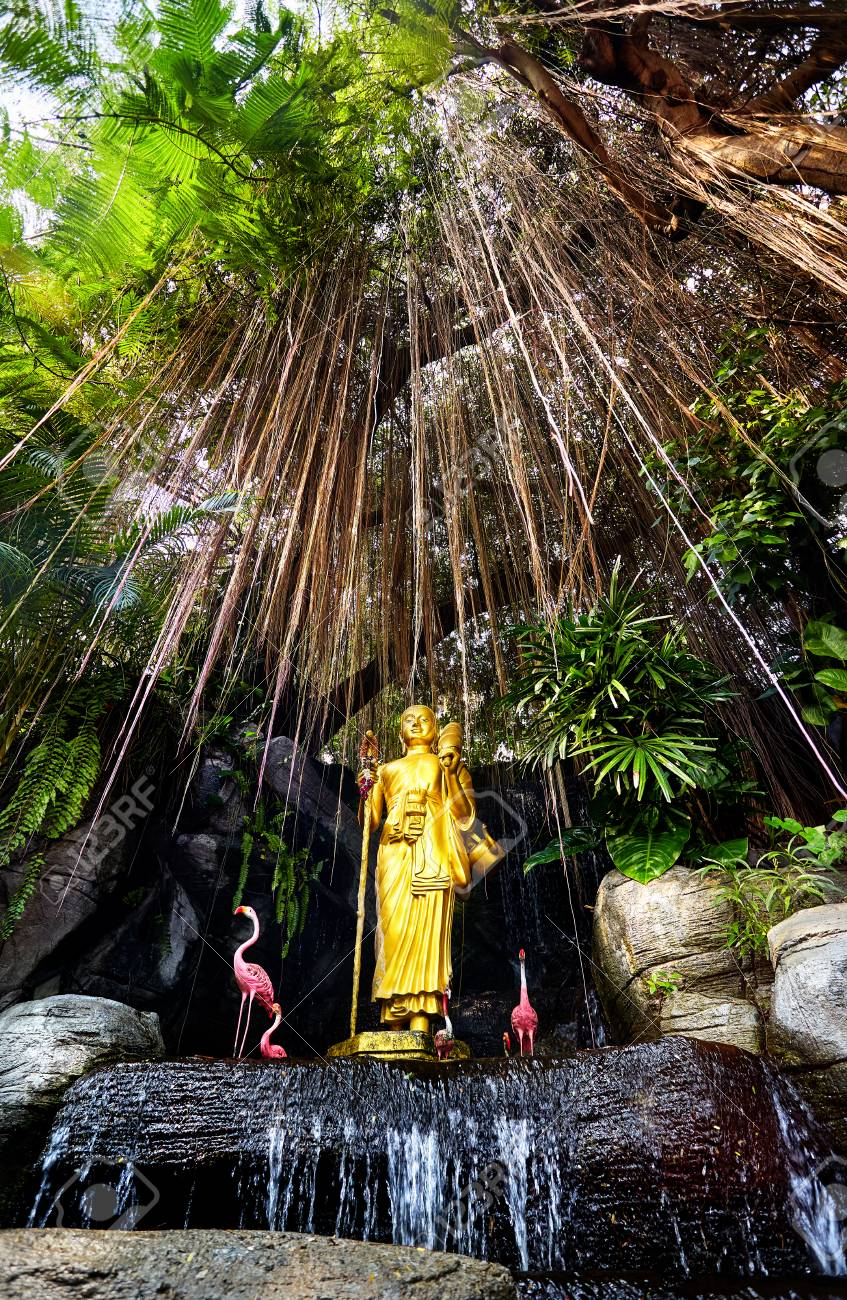 Golden Buddha Statue In The Tropical Garden With Waterfall In ...