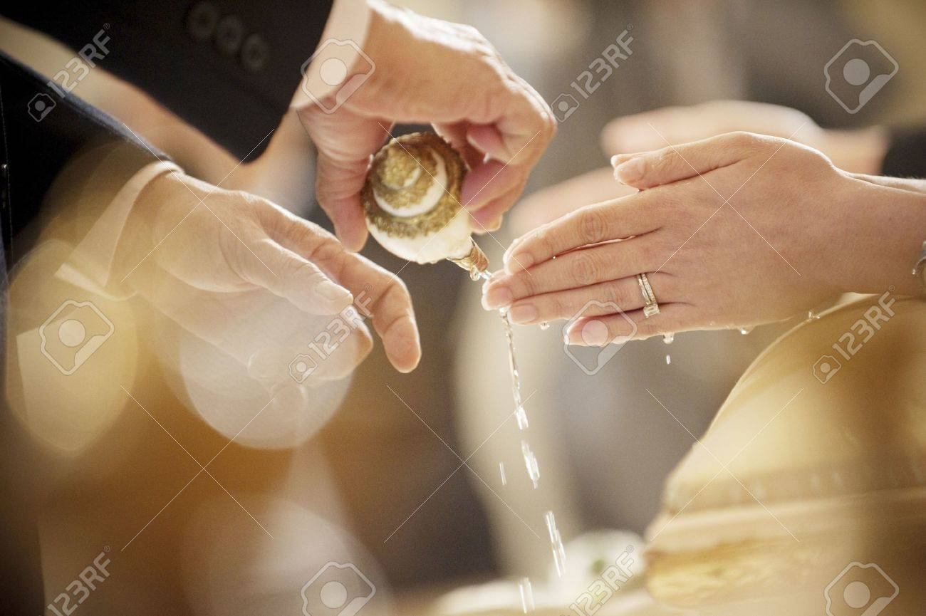 Thai wedding hand of a bride receiving holy water from elders with wedding ring on her finger Stock Photo - 18775627