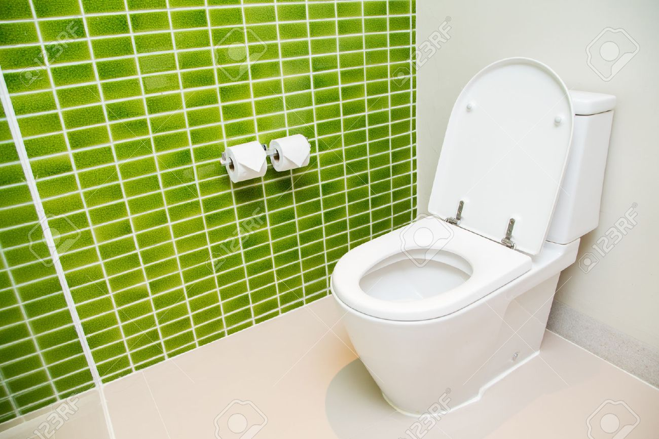 Clean, white toilet and paper rolls with Lime green mosaic tiles wall Stock Photo - 45938361