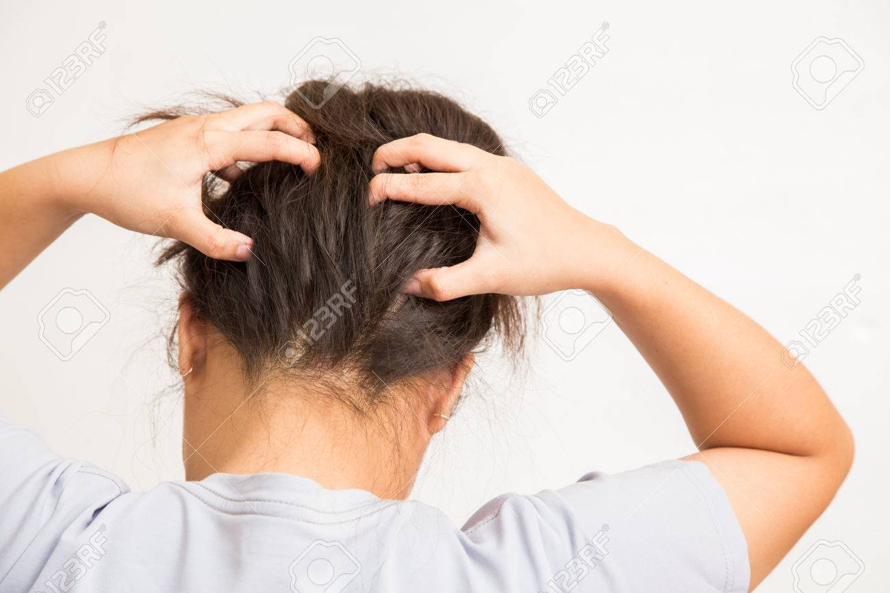 Woman suffering from an headache itching her head Stock Photo - 57261728