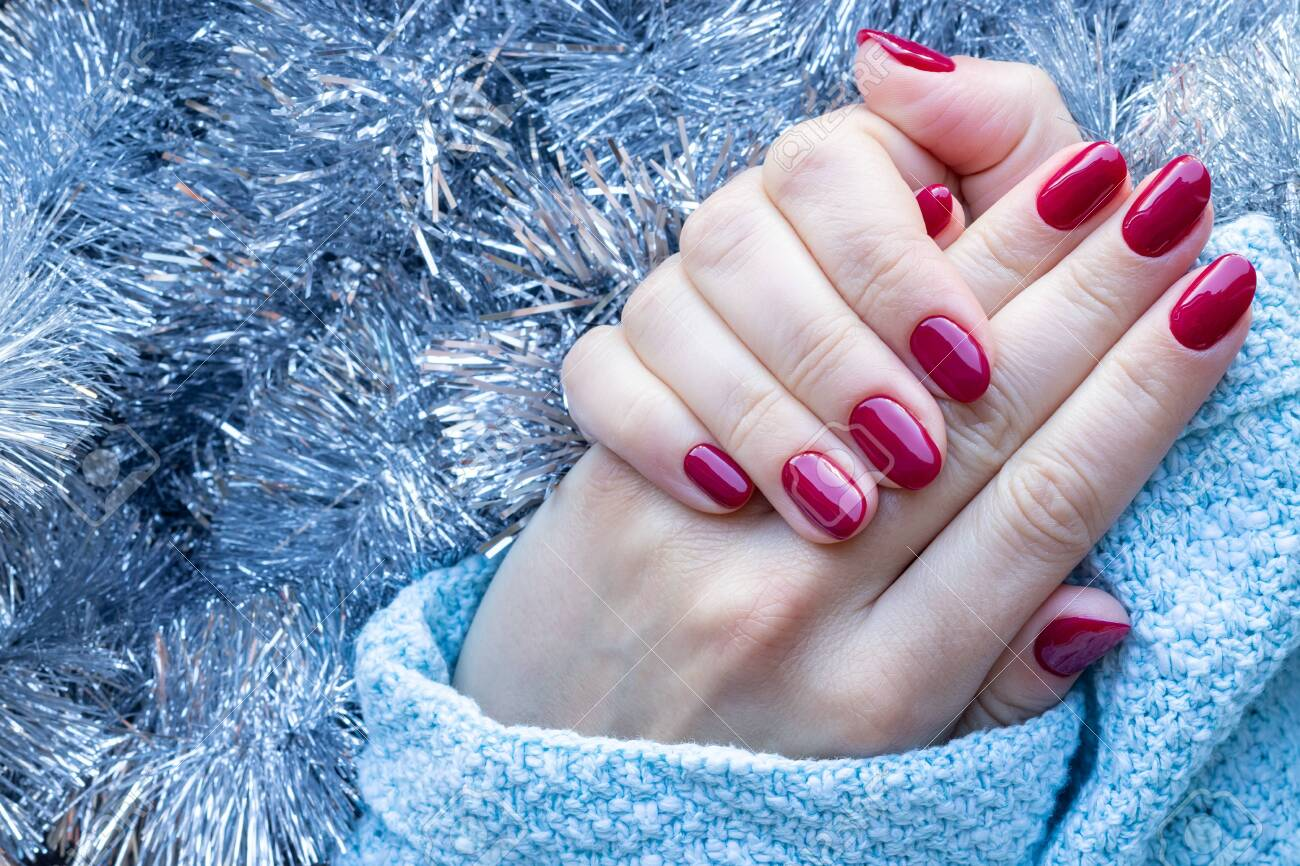 Female hands in a blue knitted sweater with a beautiful glossy manicure - burgundy, dark red, cherry color nails on background of silver Christmas tinsel garland with copy space - 155736770