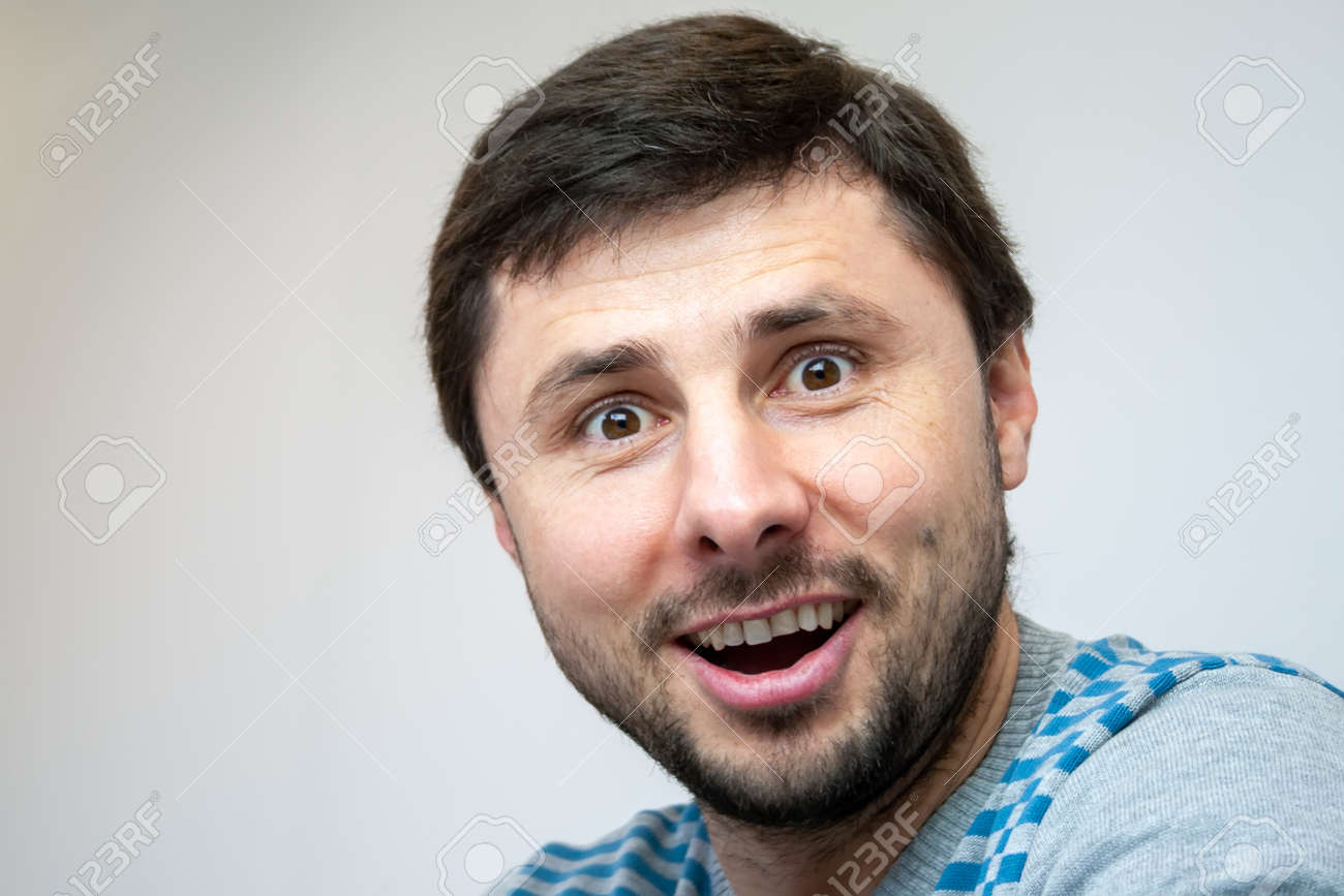Overjoyed smiling handsome bearded man looks surprised in camera - 156753156