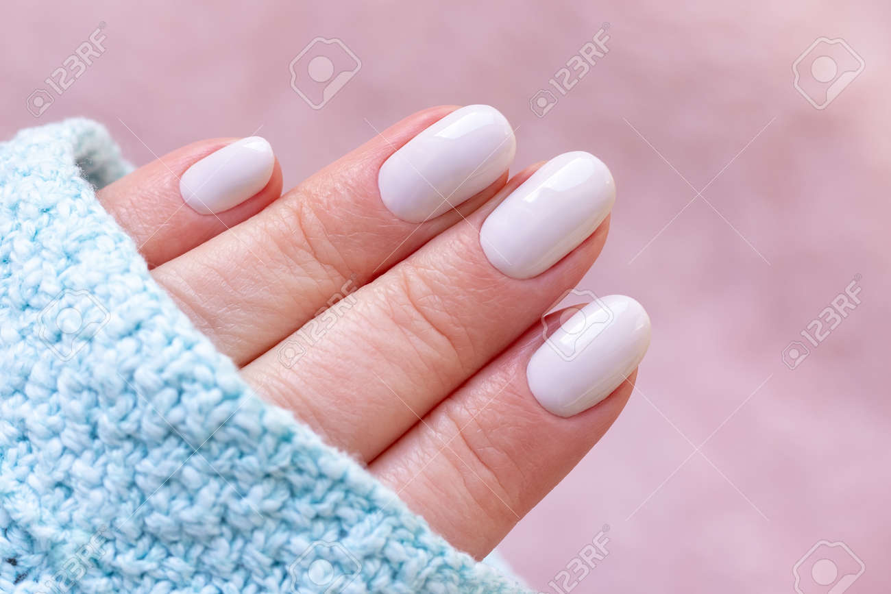 Female hand in blue knitted sweater with beautiful manicure - white ivory nails on blurred pale pink background - 169497553