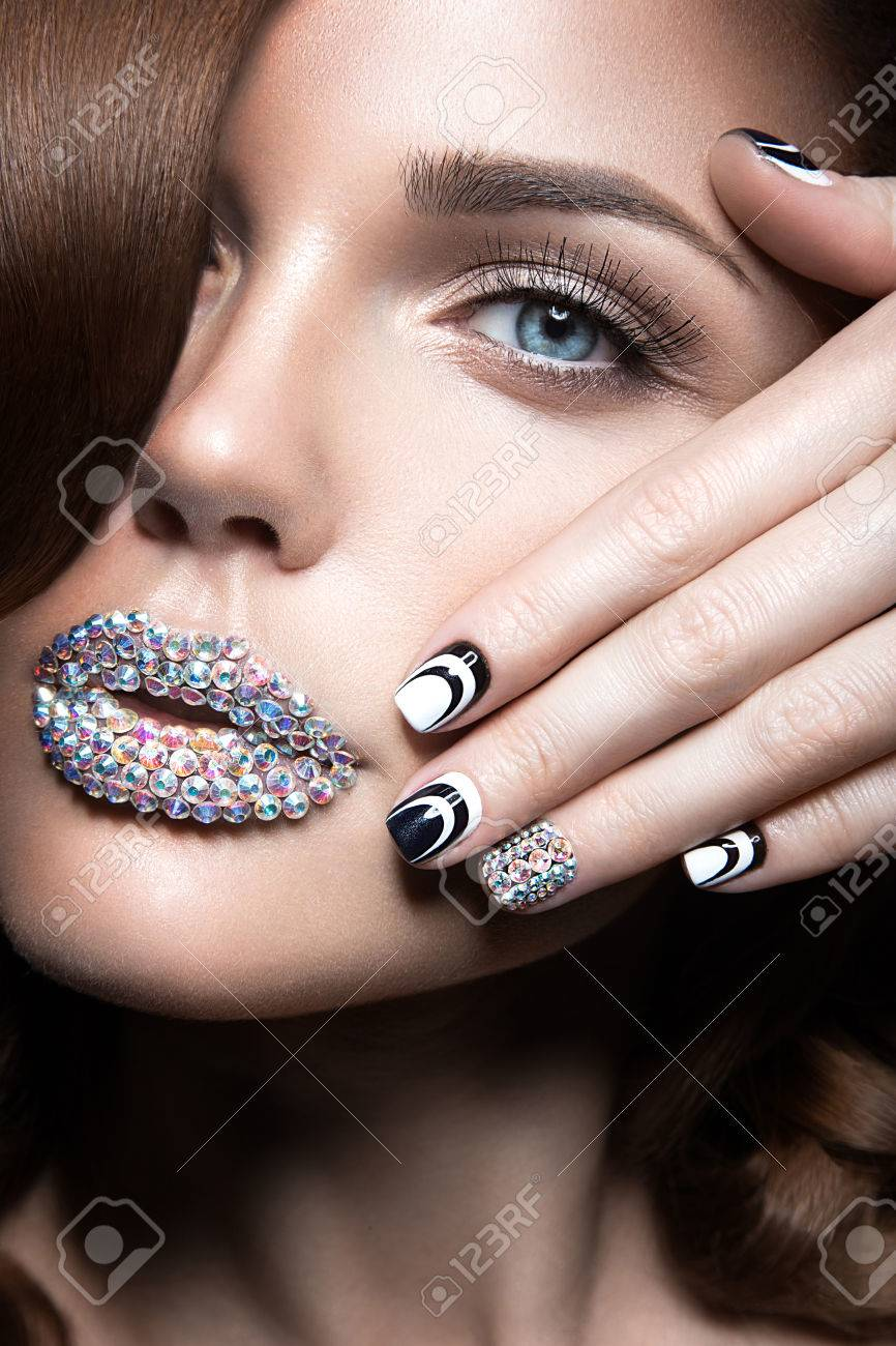 Beautiful girl with bright nails and lips of crystals long eyelashes and curls. Beauty face. - 40479725